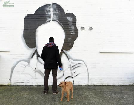 یک مرد و سگش در حال مشاهده نقاشی دیواری شاهزاده لیلا شخصیت فیلم جنگ ستارگان - بلفاست ایرلند شمالی