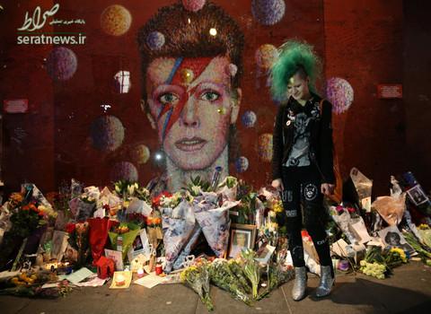 هوادار دیوید بویی  موسیقیدان و خواننده در اولین سالمرگ او مقابل یک نقاشی دیواری در جنوب لندن
