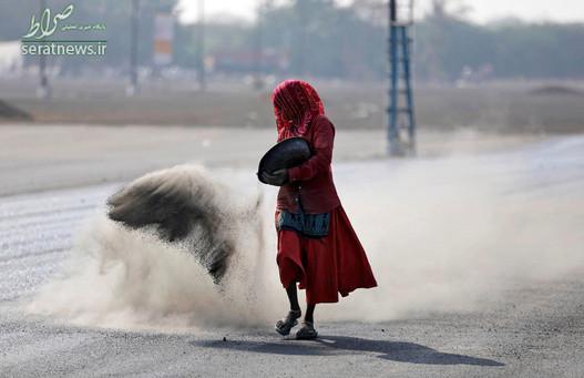 یک زن در حال پاشیدن ترکیبی از خاکستر، پودر بتن و سیمان پیش از آسفالت کردن یک جاده در احمدآباد هند