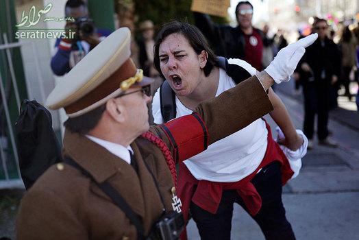 فریاد یک زن بر سر مردی که در حال احترام گذاشتن به سبک هیتلری است، در جریان تظاهرات علیه دونالد ترامپ - لاس و گاس آمریکا
