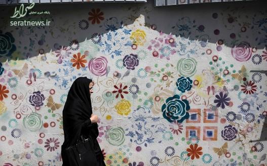 یک زن ایرانی در حال عبور از مقابل یک نقاشی دیواری در تهران