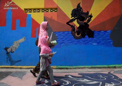 یک زن و دختر در حال عبور از کنار یک دیوار نقاشی شده در روستایی در اندونزی