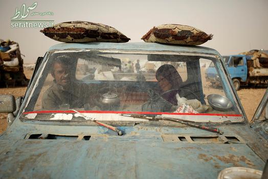 یک زن و شوهر فراری از رقه سوار بر یک خودرو در اردوگاه عین عیسی