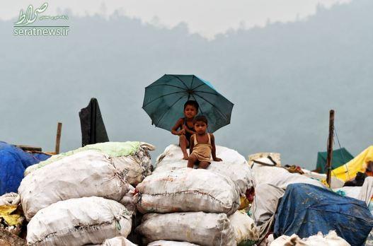کودکان نشسته بر روی کیسه های پر شده از مواد قابل بازیافت در یک محل دفن زباله - گواهاتی، هند
