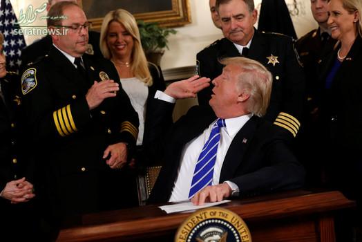 دست دادن دونالد ترامپ رییس جمهور آمریکا با یک مقام اف بی آی پیش از امضای یک لایحه در کاخ سفید