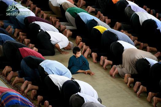 یک پسربچه نشسته در میان صفوف نمازگزاران در مسجدی در پوتراجایای مالزی
